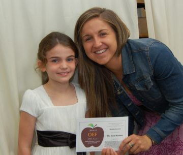 Small student in white dress with teacher, bent over, both holding APPLE award