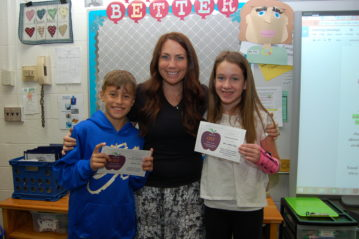 Boy in blue hoodie, Teacher, girl with pink wrist brace, showcasing their APPLE Awards to their teacher