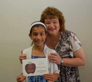 Teacher standing behind student holding APPLE Award, both smiling broadly