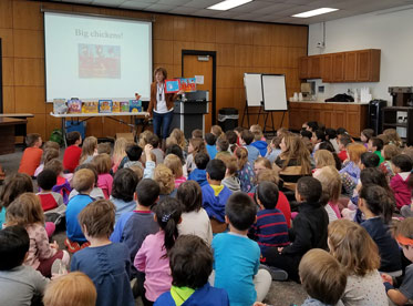 author reading book to large group of seated children, indoors