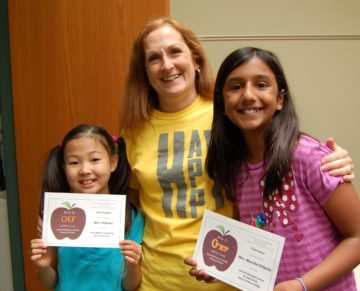 BW teacher in yellow shirt with arms around two students, each holding an APPLE Award