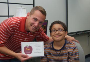 Teacher in red shirt holding APPLE award with student, seated, wearing glasses