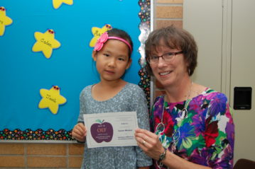 Young student, wearing bright pink hair bow and holding APPLE Award with her teacher at Cornell
