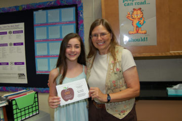 Teacher and student, standing both holding APPLE Award