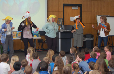 Four teachers wearing chicken hats, standing in front of seated children