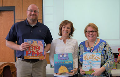 Three people holding books indoors in front of a white screen