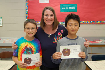 Kinawa Teacher Jocelyn Mankowski, posing with two students who are holding APPLE Awards