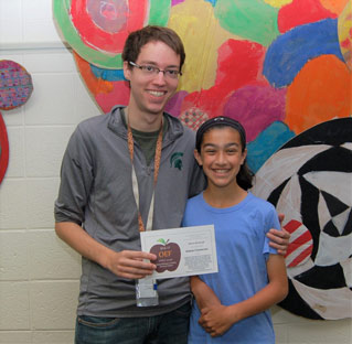 Teacher standing with student, both holding APPLE award