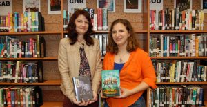 OHS English teacher Amy Huntley and OHS graduate Katie Slivensky, each holding the books they authored, in the OHS library