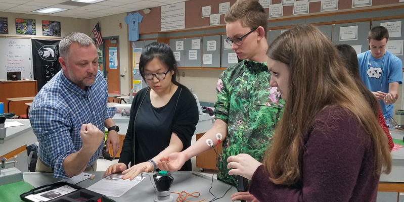 Teacher showing students scientific equipment in OHS classroom