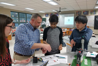 OHS teacher in blue shirt showing two students how to use scientific equipment
