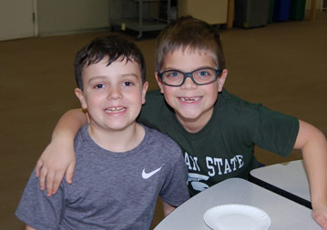 Two young boys, one with his arm around the other, sitting at a table