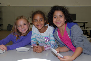 3 elementary students sitting at table, smiling at camera