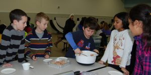 students huddled around boy, stirring contents of a bowl