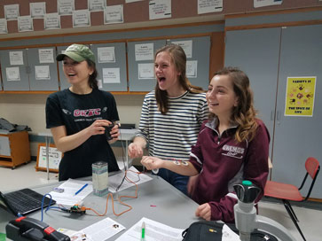 3 OHS students laughing while using scientific equipment