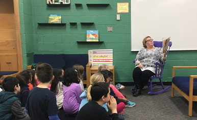 woman in rocking chair, reading to students seated on floor