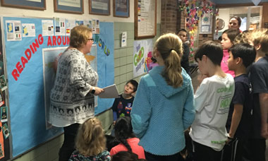 teacher pointing at wall map in front of group of students