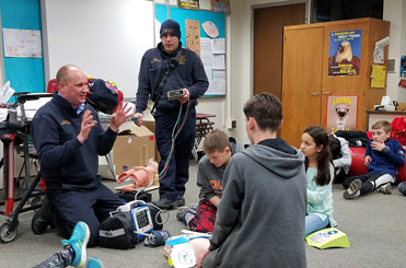 Two adult paramedics with CPR equipment demonstrating techniques with several students on a classroom floor
