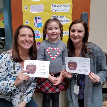 Two kneeling teachers holding APPLE Awards with adorable pig-tailed student standing in between