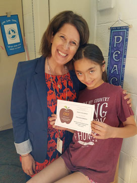 Teacher and student, standing very close; girl is holding APPLE Award and smiling shyly