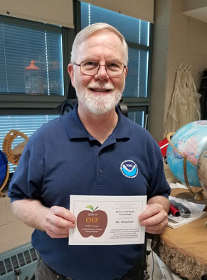 White man, beard and glasses in blue shirt, holding an APPLE Award. Standing next to globe in classroom