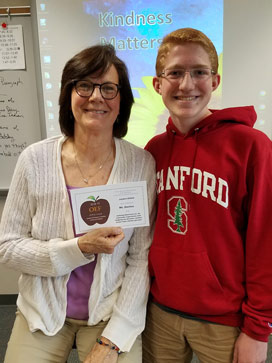 White teacher, dark hair and glasses, holding an APPLE Award next to student (red hair and glasses, wearing a red Standford hoodie)