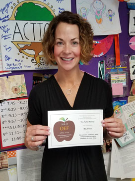 White woman, curly hair, black shirt, holding an APPLE Award, standing in front of busy bulletin board