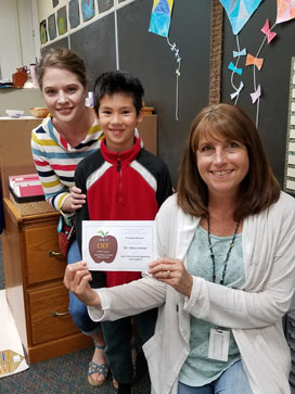 Two teachers with student standing in between. One teacher holding an APPLE Award. All smiling