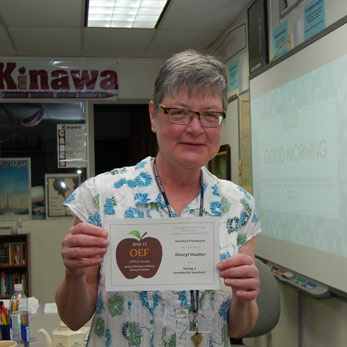 White woman, flowered shirt and glasses, holding an APPLE Award