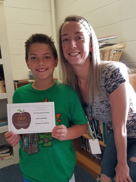 Boy in green shirt holding an APPLE Award with teacher smiling in background