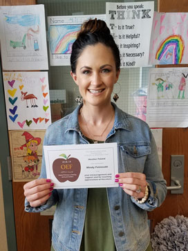 White woman, dark hair pulled up in a knot, denim jacket, holding an APPLE award, standing in front of youth artwork