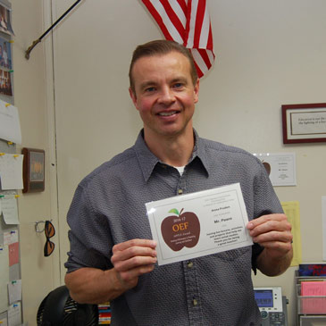 White man in gray shirt, holding APPLE Award. Flag in background