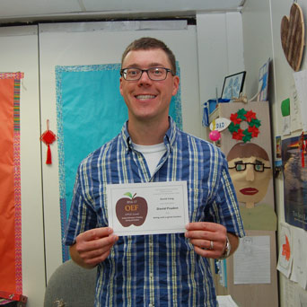 White man, glasses, plaid shirt, holding an APPLE Award