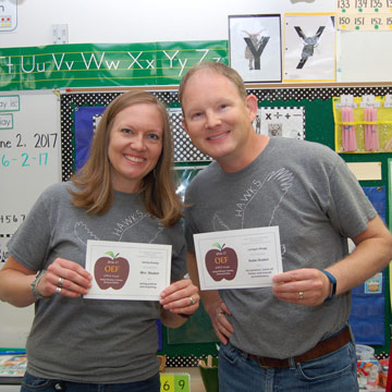 Couple, each in gray shirts, holding APPLE Awards and smiling