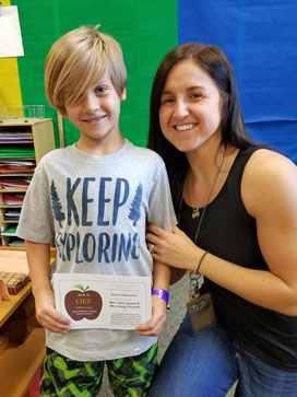 "Student in ""Keep Exploring"" tee shirt, holding an APPLE Award beside smiling teacher"