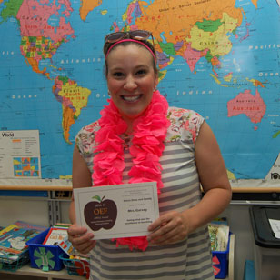 Woman wearing bright pink lei with glasses on her head, holding APPLE Award. World map in background
